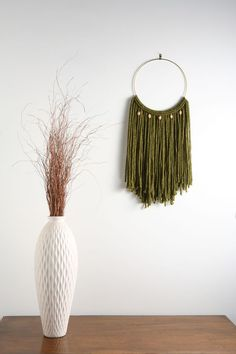 """Emerald Green Macrame Wall Hanging Tapestry on 10"""" Brass Hoop w/ Wood Beads. MATERIALS: - Size: Large - Materials: 100% acrylic blend fibers - 10"""" brass ring - wooden beads *(The color of the wooden beads may vary)* Dimensions: 13""""w x 28""""h ____________________ The """"Sultry Boho Chic"""" Collection exudes everything sexy and girlie! These pieces can be used to accessorize almost any style, but is definitely suited for those lovers of the Bohemian / Boho-Chic and Shabby Chic styles."""