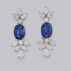 A PAIR OF SAPPHIRE AND DIAMOND EAR PENDANTS   Each set with an oval-shaped sapphire weighing 10.35 and 10.29 carats to the pear-shaped and brilliant-cut diamond surmount and terminal, 4.5 cm long