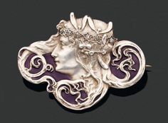 Lalique - Signed Oval Brooch representing a woman in profile with hair held in a coronet of rose-cut diamonds and mistletoe. Background in purple enamel. The reverse also in purple enamel.      Pierre Bergé & associés
