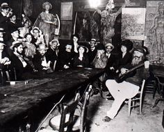 "Inside the Lapin Agile.  Frédé is sitting on the right with a guitar; on the wall to the left of the large crucifix is the Picasso painting ""Au Lapin Agile."""