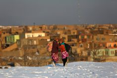Girls walk through snow in Kabul, Afghanistan - by Mohammad Ismail/Reuters