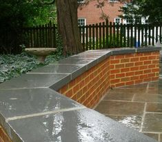 Brick retaining wall with blue stone tops.