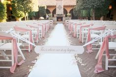 """Outdoor wedding ceremony tied off with """"This is where our story begins..."""" sign; rose pink diagonal chair ties and blush rose petals lining white aisle runner 