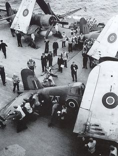 """Ship's officers and 1834 squadron pilots watch Corsair """"7T"""" of 1834 being moved by deck handlers on HMS Victorious, 1945"""