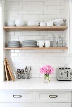 Les étagères en bois naturel et les planches à découper simplement placées ajoutent chaleur à cette cuisine blanche.