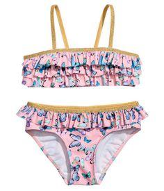 Rosa/Fjärilar. En bikini med tryckt mönster, volanger och glittriga kantband. Topp med smala axelband och foder fram. Bikinitrosor med volang upptill och