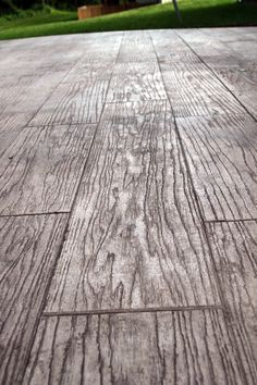 No that is not hardwood, it is stamped concrete! found this idea on a local contractor's website. We contacted him immediately to get an estimate. I have a love for wood that is dark and rustic, so to be able to have the warmth of a deck combined with the ease of concrete? Heavenly! I've never seen anything like this before