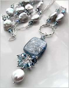 Graceful, opera-length white coin pearl necklace with decorative sterling silver chain, blue kyanite gemstone pendant and Swarovski crystal accents.