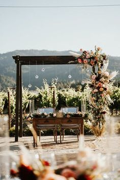 Rustic arch with boho florals, hanging bulbs, and a vintage style sweetheart table | Tre Posti Saint Helena, CA