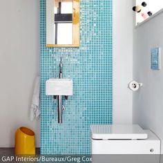 Ein frischer und farbenfroher Look wird in diesem WC mit Hilfe von blauen Mosaikfliesen und einem gelben Spiegelschrank mit passendem Mülleimer geschaffen.  …