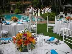 Bright colorful table arrangements accented with teal dinner napkins.