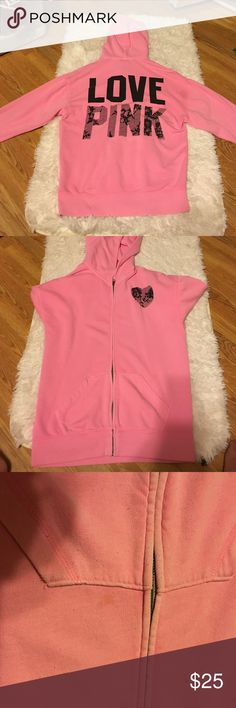 Pink VS Hoodie Pink hoodie with black lace design in the word Pink. Full zip, pull strings are missing. There's a few spots in picture and one more tiny one on the back of the other arm (not pictured I ran out of room) but they are barely noticeable and reflected in the price. IMPORTANT: the size says XS but is not true to size. I wear a medium or large and it's a little baggy. PINK Victoria's Secret Jackets & Coats