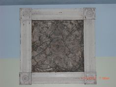 An antique tin ceiling tile framed in antique moldings makes a great art piece.