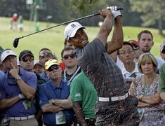 Tiger Woods hits out of the rough off the first fairway during the first round the Masters golf tournament Thursday, April 5, 2012, in Augusta, Ga.