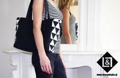 Daily Bag Black en white: hippe black en white, leren Daily Bag met stoere zwart -wit triangel stof op de zijkanten van de tas. Handig vak voor uw sleutels en kleine dingen mag natuurlijk niet ontbreken. De tas is te sluiten door middel van drukknopen. Ideale tas voor als je gaat shoppen en je er ook nog eens trendy uit wilt zien.