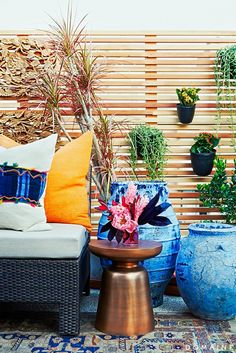 Jen Atkins Rooftop by @consortdesign // Side table with flowers and blue planters.