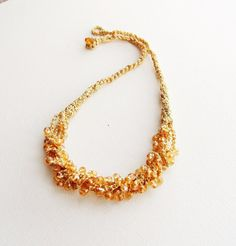 Hand crocheted with metalized golden viscose yarn and beaded with goldcolored Swarovski Crystals this necklace is light and comfortable to wear.