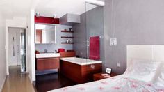 """Éclairage naturel Cette ouverture parée d'une vitre rouge permet de profiter de la lumière du jour dans les WC attenants. - Le couloir dessert le hammam, les WC d'invités puis la zone privative, composée des toilettes et de la chambre (linge de lit """"Coral Print"""", Zara Home) avec sa salle de bains. Cet espace peut être clos par la porte en verre soufflé de Murano (Atelier Carrisi Edizioni)."""