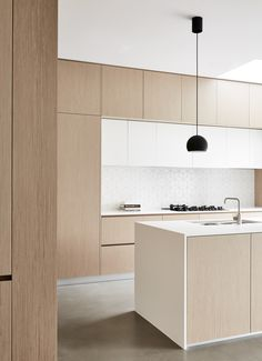 Kitchen - wooden finish - white top - white tiles - concrete flooring - minimal design - recessed handles