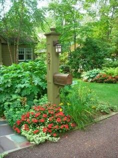 Tall mail box topped with a solar light and surrounded by a delightful flower garden
