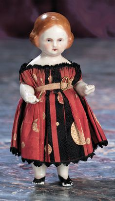 """German All-Porcelain Doll 6"""" (15 cm.) One-piece all-porcelain doll with slight pink tinting is standing with small fists closed in front,light brown sculpted hair in short finger curls,painted tiny blue eyes,red and black upper eyeliner,closed mouth,painted black shoes. Comments: Germany,circa 1865. Value Points: unusual facial painting and hair color,endearing antique costume includes silk gown and undergarments."""