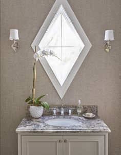 Taupe powder room features walls clad in taupe herringbone wallpaper fitted with a diamond shaped window illuminated by polished nickel diamond wall sconces placed over a light taupe single washstand topped with gray granite and a white prickly vase filled with an orchid.