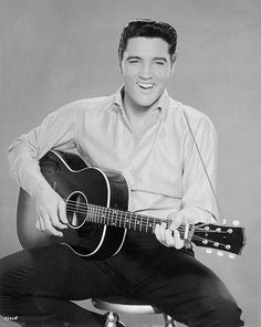 Presley strums an acoustic guitar while posing for a portrait in 1962
