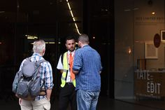 People talk to a security guard securing the entrance to the Tate Modern gallery in London on August 4, 2019 after it was put on lock down and evacuated after an incident involving a child falling from height and being airlifted to hospital. A teenager was arrested over the incident, police said, without giving any details of the child's condition. (Photo by Daniel SORABJI / AFP) (Photo credit should read DANIEL SORABJI/AFP/Getty Images)