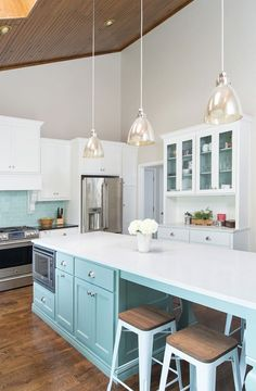 Pale turquoise kitchen cabinets with white glass front cabinets. Love the contrast against the paneled wood ceiling. Microwave in island