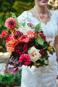 Lush dahlia, peony, and garden rose bouquet in oranges and berry colors by Sarah Winward. Photo by Travis J