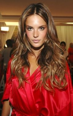 Latte-brown hair color on long curly hairstyle | with hazel eyes and olive skin tone you can have a blend of medium brown and dark brown base.