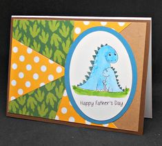 A small and a large blue dinosaur have glow in the dark enamel dots on their backs and the saying 'Happy Father's Day' below them in a white oval with a green border. The background is a pattern of yellow and white polka dots and green dino footprints on green and brown paper.