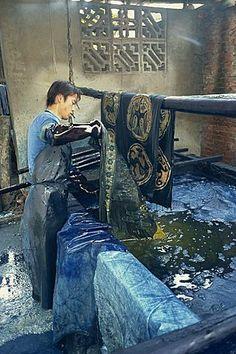 Dipping batik in an indigo vat, Guizhou, China, Asia