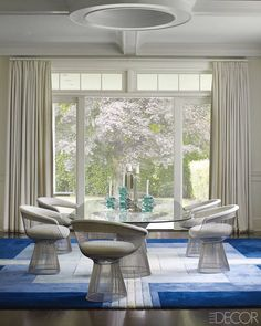 Warren Platner armchairs and dining table with a custom glass top are by Knoll, and the vintage rug is by Edward Fields. - ELLEDecor.com