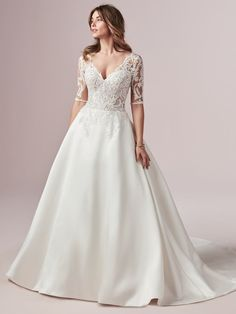 This stunning Mikado A-line wedding dress featuring pockets has a plunging illusion sweetheart neckline, a delicately embroidered bodice and gorgeous illusion lace sleeves. A beautiful captivating keyhole back and covered buttons over the zip. Lace Wedding Dress With Sleeves, Maggie Sottero Wedding Dresses, Princess Wedding Dresses, Designer Wedding Dresses, Bridal Dresses, Wedding Gowns, Bridesmaid Dresses, Dresses With Sleeves, Lace Sleeves