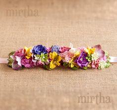 Cinturón de flores de papel y tela sobre lazo con una combinación muy primaveral. Mezcla hojas y flores como rosas, peonías, lirios, hortensias..., el favorito de nuestras invitadas