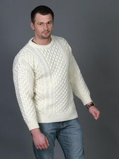 Made from 100% Soft Merino Wool  This Traditional Aran crew neck sweater is one of the greatest sellers in our Aran knitwear section. It follows all the traditional Aran knitting patterns. Along the centre panel of the body the honeycomb Aran stitch flows, signifying the hard working bee or the hard work of a fisherman. On either side of this centre panelling there are rows of Irish cable Aran stitches symbolizing the fisherman's ropes, the link to life.The sweater can be worn by men and…