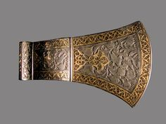 Persian axe head with carved decoration and gold inlay.