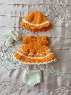 Hand knitted dolls outfit to fit a 5 Berenguer Itty Bitty baby doll/Cupcake doll. Knitted in tangerine and contrasting cream coloured yarn, and consisting of a dress, hat, pants and shoes. The dress is knitted in tangerine with cream patterning around the front and back of the skirt. There is a back opening which fastens with two tiny pearls, and cream crocheted scalloped edging all around the bottom of the skirt. A matching wide brimmed hat in tangerine with a cream band. A pair of ...