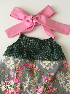 This halter romper is just perfect for spring, big sister baby announcements and birthday pictures. The bodice has a microfloral print on a dark green background. The green and pink from the bodice picks up the colors in the contrasting romper bottom.  Easy Wear--simply slip in feet through the elastic back and ruffle leg openings then tie the sewn-in pink halter strap behind the neck into a big bow. The bow can be left intact for independent dressers. No snaps, so dressing after diaper…
