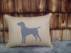 This handmade burlap pillow features a hand stenciled silhouette of a Weimaraner, shown here in gray and barn red (middle photo) on natural