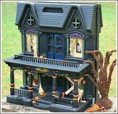 Halloween decorations - Take an old plastic doll house and turn it into a haunted house with spray paint and Halloween accessories!