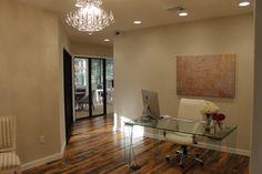 Reception area.  #reclaimed #hardwood #chandelier #glass #desk #modern #office