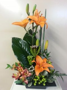 Triangular arrangement with lilies, alstroemeria, berzellia, equisetum and mixed foliages.
