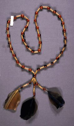 Brazil | Necklace from the Pukobye people.   Long strand of alternating, large red/black ormosia seed and elongated beads of cane, terminating in 3 strand pendant strand of cane pieces, pati palm and ormosia seeds ends in blue/brown feathers.  Sao Jose, Timbira, Maranhao. | Date collected 1984.