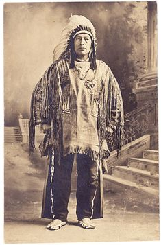 """Circa 1910 real photo postcard. This individual is identified on the back as: """"Big Bear, Iroquois tribe, Caughnawaga, Canada."""" His Plains Indian attire suggest he may have been involved in the Wild West Shows. He is wearing a heart shaped piece of fancy Mohawk beadwork on his shirt."""