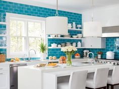 """The ocean blue backsplash tiles are large and graphic and bright. At 4 inches by 8 inches (compared to 3- by 8-inch subway tiles), """"both the size and color were daring, even for me, but that shade seemed right for this house,"""" says Braff, who also liked t"""