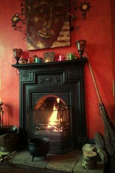 Gothic home with red walls, black fireplace, witches cauldron, and skeleton painting above mantel. Witch Cottage, Witch House, Black Fireplace, Country Fireplace, Cottage Fireplace, Small Fireplace, Fireplace Mantle, Fireplace Surrounds, Fireplace Design
