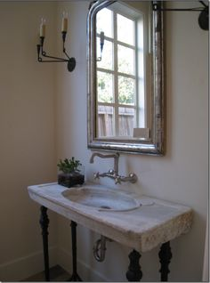 The powder room has an antique sink on iron legs with wall hung fixtures. Simple three armed black iron sconces flank the silver leafed Louis Phillipe mirror. Simple yet elegant. Octagon House, Wall Mount Faucet, Wall Taps, Wall Sconces, Mirrors, Decoration Design, Sink Faucets, Vanity Sink, Guest Bath