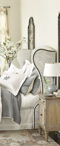 Grey and white paisley headboard. White pom pom trimmed grey quilted bedding. Nail head headboard.